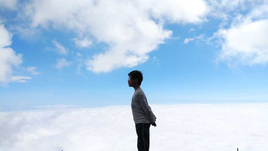 Side view of boy standing against clouds and sky