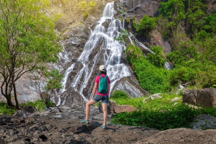 Full length of woman looking at waterfall