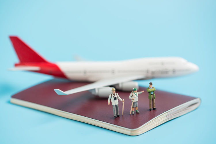 Close-up of hiker figurines on passport with airplane model against blue background