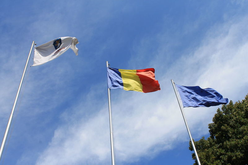 Low angle view of waving flags against sky