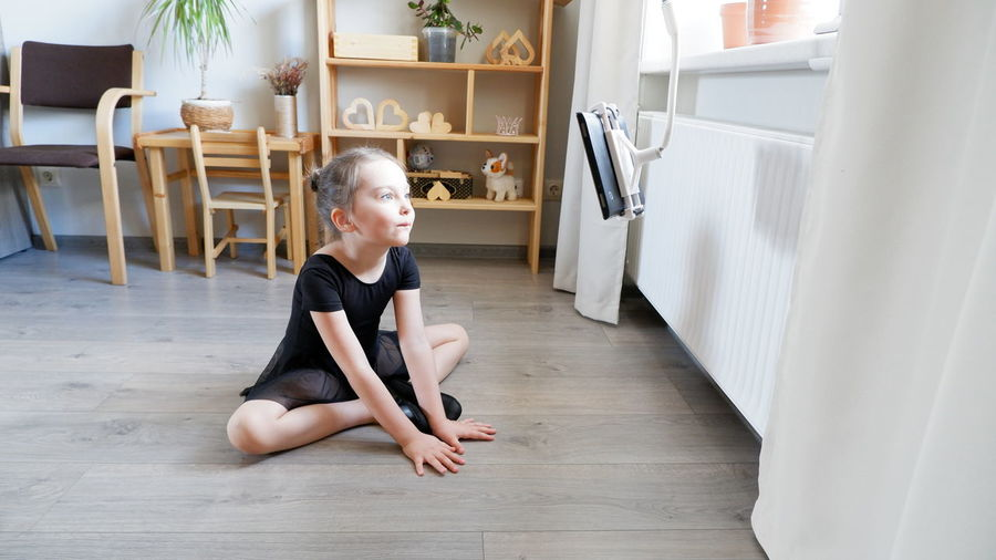 Cute girl looking away while sitting on hardwood floor at home