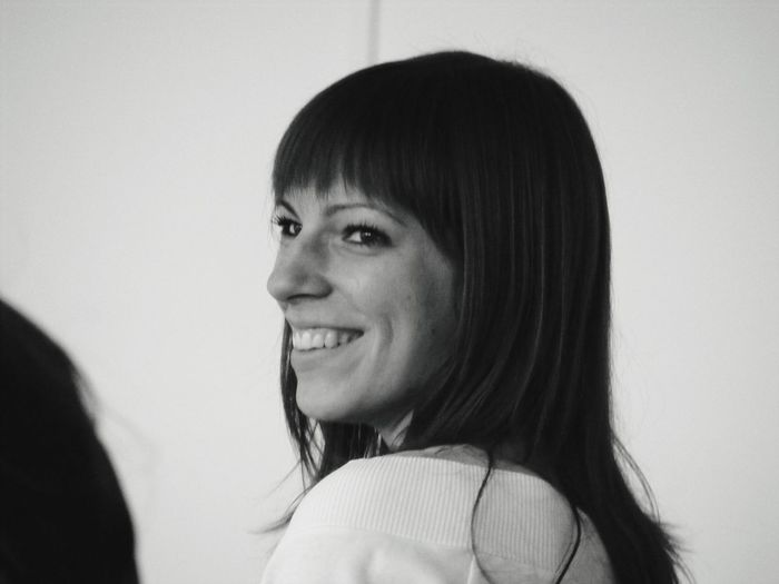 Side view of smiling young woman looking away while standing against wall