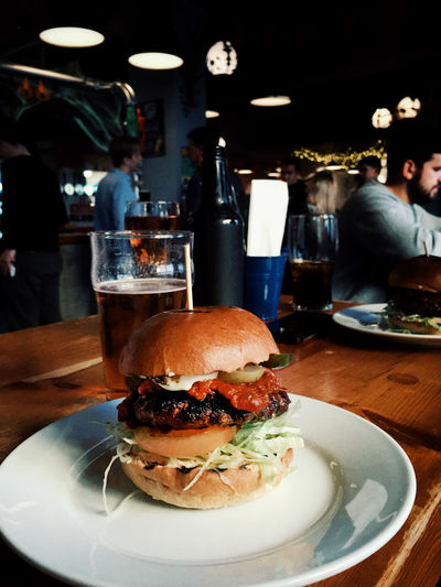 Get in me Food And Drink Fast Food Burger Unhealthy Eating Food Table Incidental People Sandwich Ready-to-eat Restaurant Plate Freshness Drink Hamburger Indoors  Business Close-up Focus On Foreground Glass Refreshment Temptation Snack