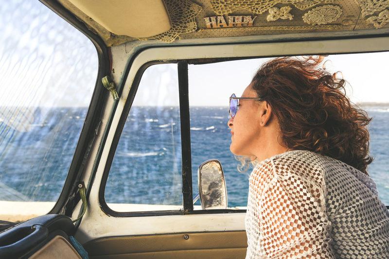 Woman looking through vehicle window