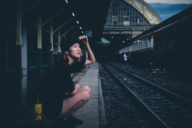 Full length of young woman crouching at railroad station platform