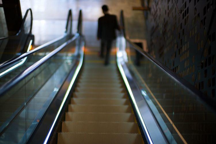 Rear view of people walking on escalator in building