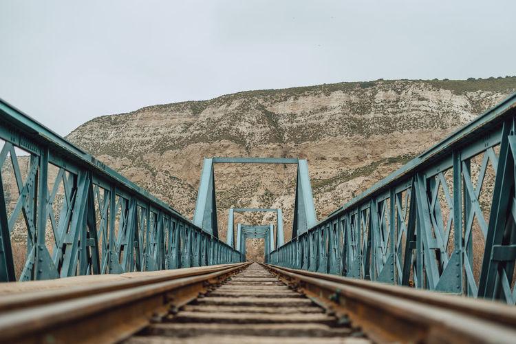 Footbridge over railroad track against sky