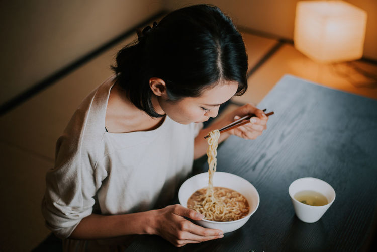 High angle view of woman eating food at restaurant