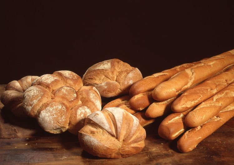 Variety of brown loaf breads on wooden table
