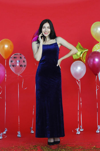 Full length of a young woman holding red balloons