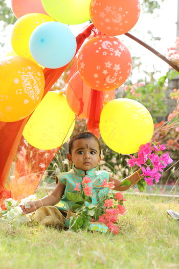 Portrait of cute girl wearing dress with balloons sitting at lawn