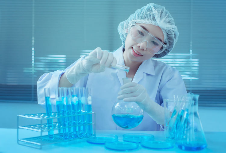 Young Female Scientist Pouring Chemical In Flask At Laboratory