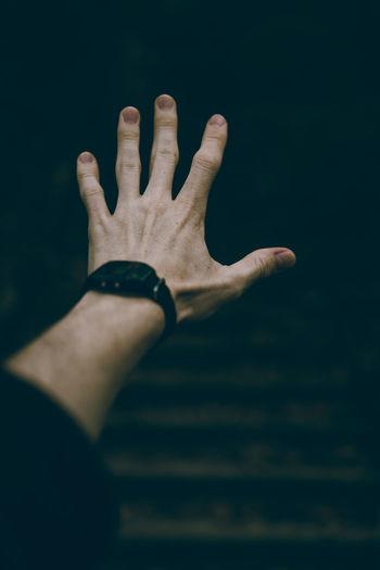 Cropped Hand Gesturing In Darkroom
