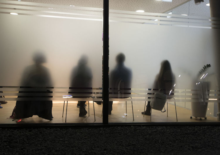 Rear view of people sitting in office seen from frosted glass wall