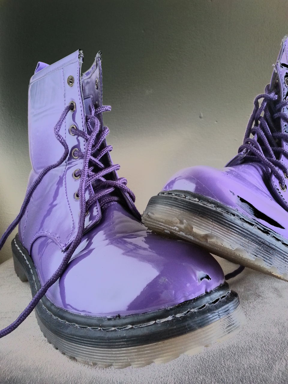 Close-Up Of Torn Purple Boots On Rug At Home