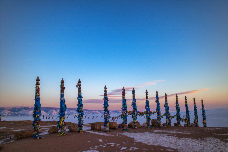 Multi colored prayer flags on bamboo poles at mountain against sky during sunset