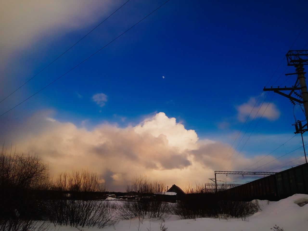 sky, winter, nature, cold temperature, beauty in nature, tranquil scene, snow, outdoors, cloud - sky, scenics, no people, tranquility, weather, connection, cable, architecture, built structure, silhouette, tree, sunset, building exterior, bare tree, lake, water, day, landscape, electricity pylon, vapor trail