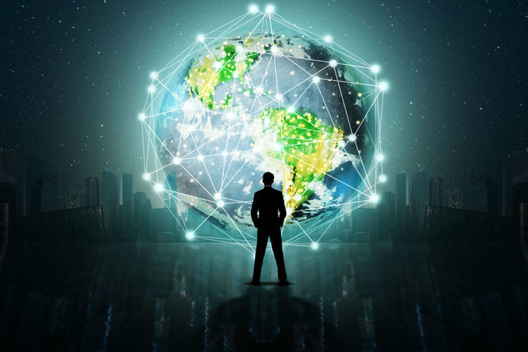 Digital composite image of silhouette businessman standing against illuminated globe at night