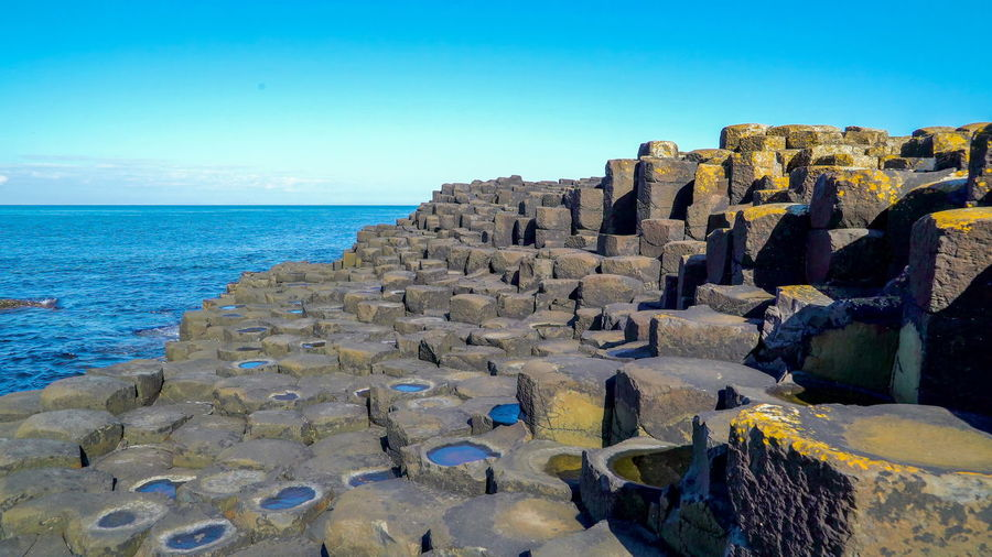 The landscape view of the rock formations in the Giants Causeway with the big ocean Sea Water Sky Horizon Over Water Scenics - Nature Land Horizon Rock Beauty In Nature Blue Nature Solid Beach Rock - Object Clear Sky Tranquil Scene No People Tranquility Day Outdoors Rocky Coastline Ireland Northern Ireland Giants Causeway Stone Rock Hexagon Travel Seascape Famous Place