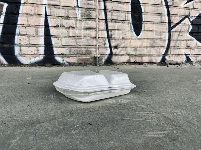 Garbage can on sidewalk against wall