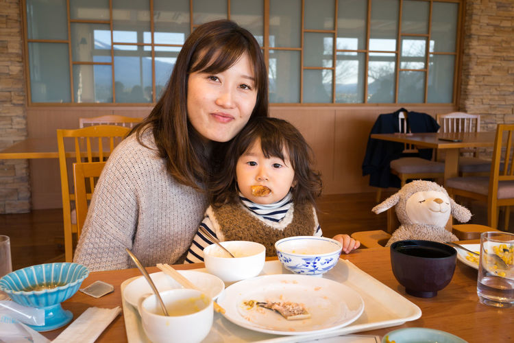 Portrait of mother with daughter eating food while sitting in restaurant