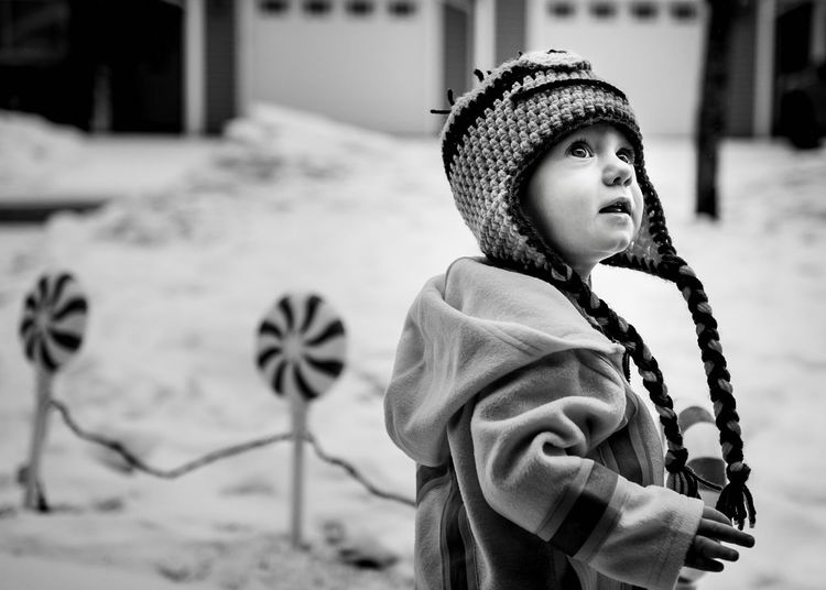 Close-Up Of Young Boy In Front Yard In Winter