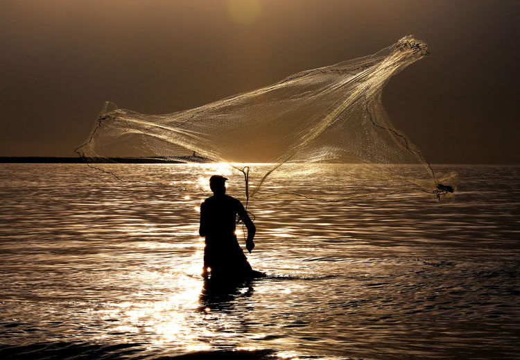 Silhouette man fishing in sea