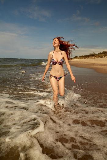 Full length of woman at beach against sky