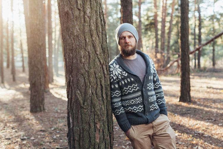 Thoughtful young man standing in forest