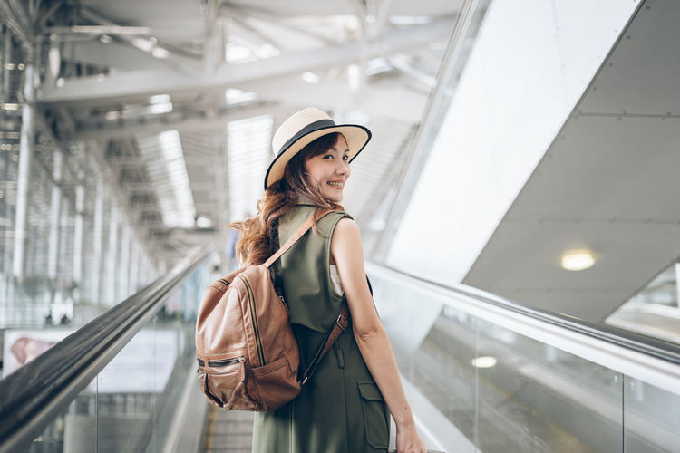 Side view of young woman standing on escalator
