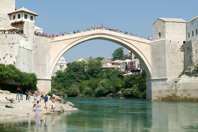 People in front of arch bridge against clear sky