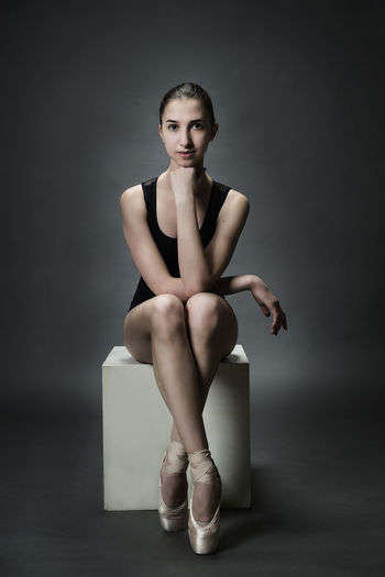 Ballerina Adult Adults Only Ballet Ballet Dancer Beautiful People Beautiful Woman Beauty Front View Full Length Gray Background Indoors  Lifestyles Looking At Camera One Person One Woman Only One Young Woman Only People Portrait Sitting Standing Studio Shot Young Adult Young Women
