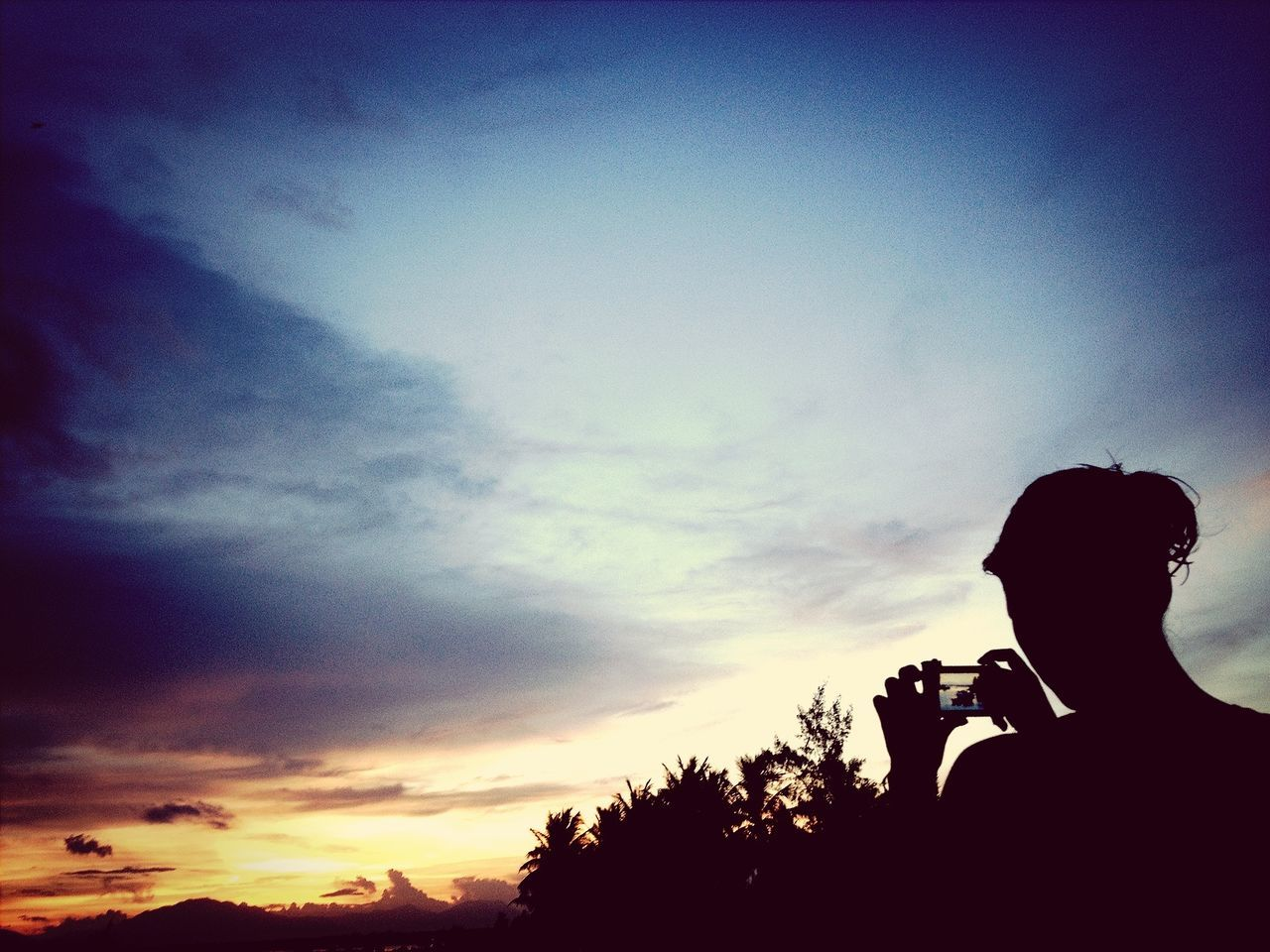 Silhouette person photographing landscape at sunset