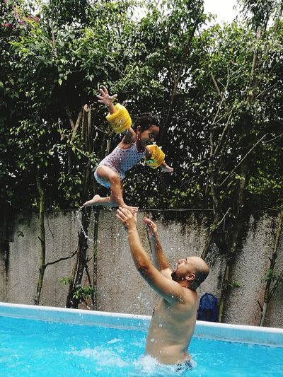 Father Playing With Daughter In Wading Pool