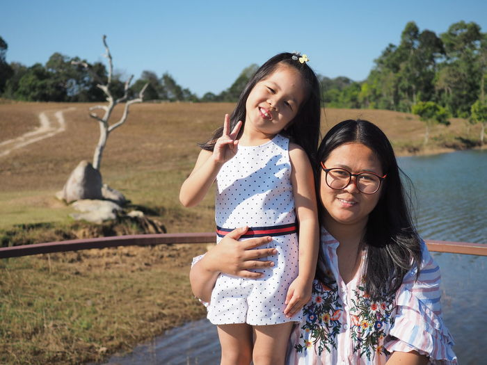 Portrait of smiling mother with cute daughter against landscape