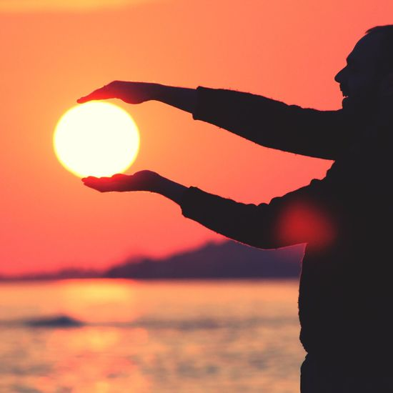 Universal play. Sunset Silhouette Sun Real People One Person Sky Beauty In Nature Sea Nature Scenics Outdoors Beach Leisure Activity Lifestyles Human Hand Sunlight Men Water Horizon Over Water One Man Only EyeEm Selects