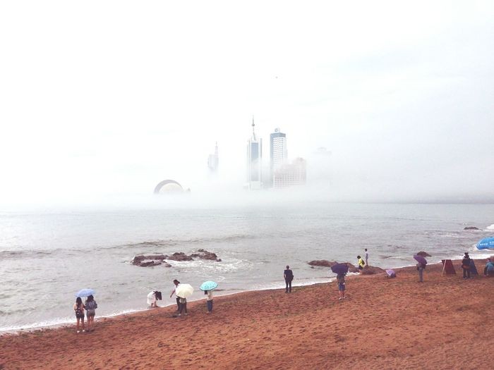 High Angle View Of People At Beach Against Skyscrapers During Foggy Weather