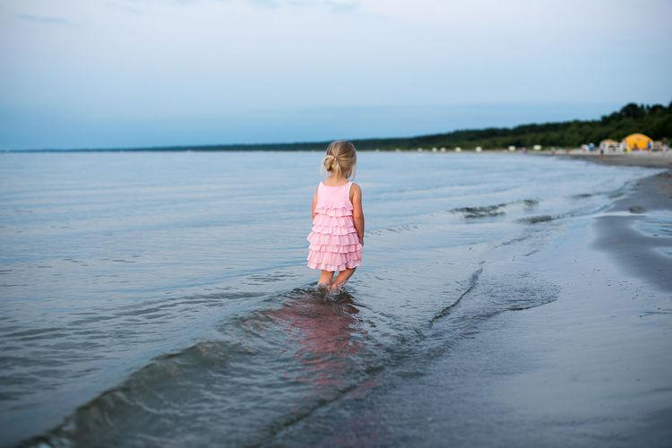 Girl wading in sea against sky