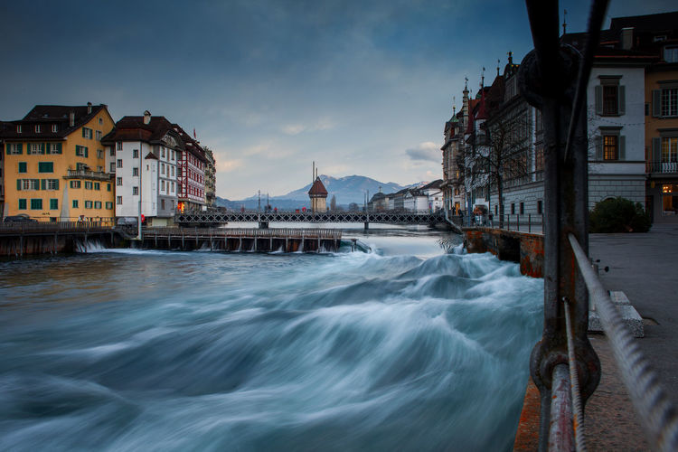 River flowing amidst buildings against cloudy sky