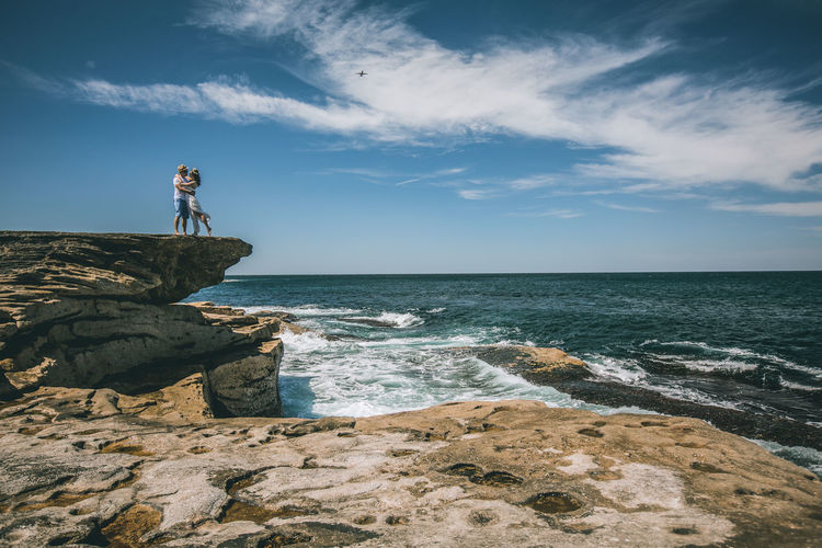 Couple on rock by sea against sky