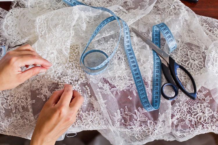 Cropped image of fashion designer making wedding dress