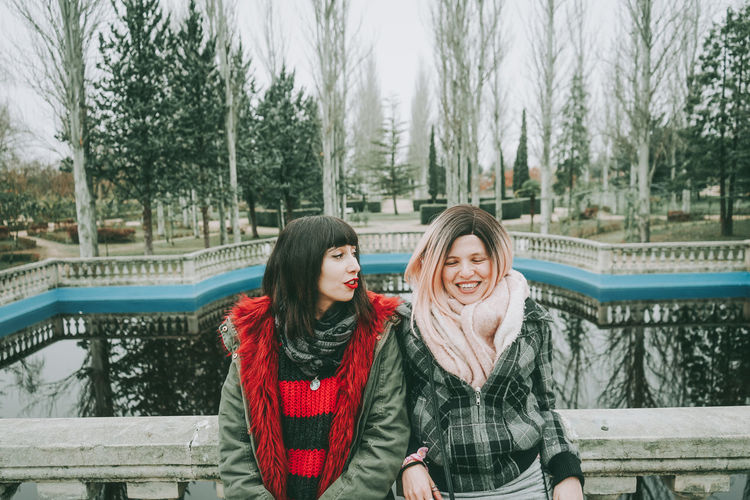 Smiling friends leaning on railing against lake during winter