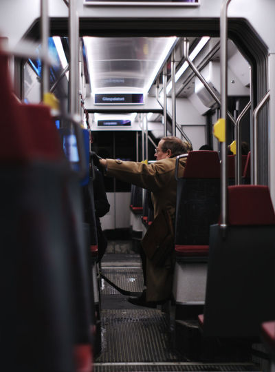 Tram ride in January Shot From Behind Warm Clothing Wool Coat Trench Coat Architecture Helsinki Finnish  Finland Sitting One Person Indoors  Travel Adult Public Transportation Mode Of Transportation Passenger Rear View Interior Tram Transportation Real People Selective Focus Subway Train Train Gh5
