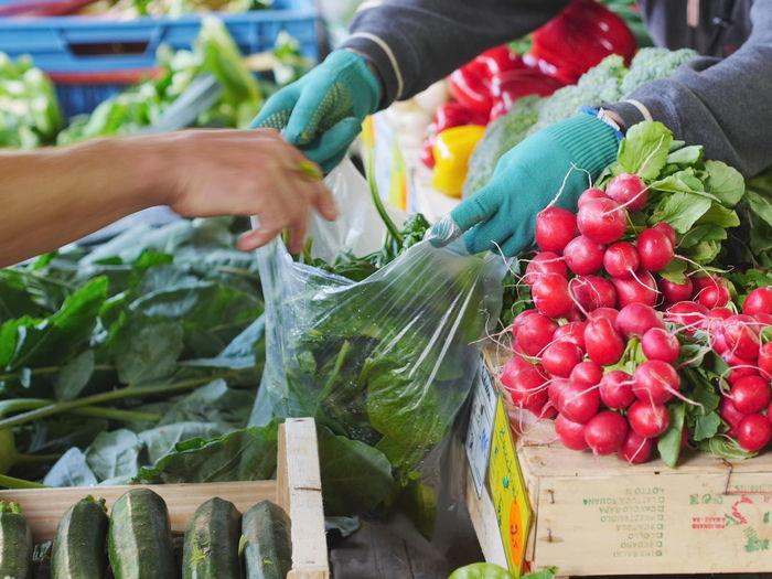 Cropped Image Of Market Vendor Giving Vegetables To Customer