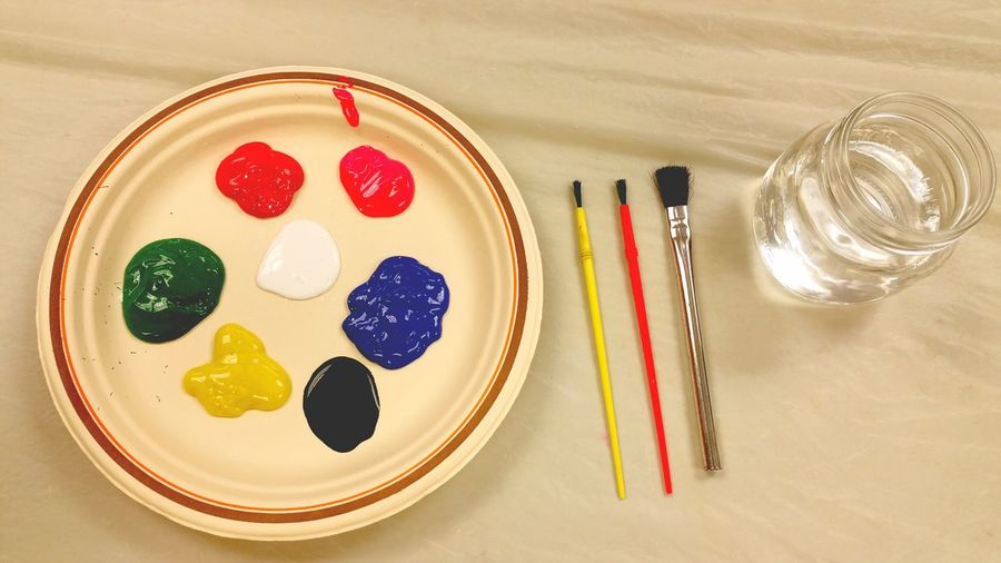 High Angle View Of Multi Colored Paints In Plate With Brushes On Table