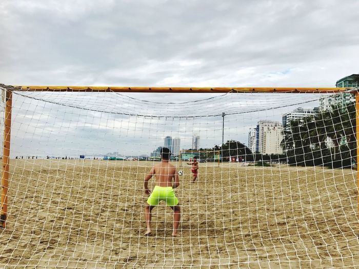 EyeEmNewHere Sky Real People Cloud - Sky Rear View Two People Men Lifestyles Leisure Activity Day Togetherness Playing Outdoors Standing Full Length Architecture Young Adult Adult People Football Soccer Beach Sport