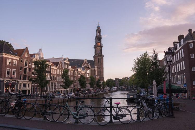 Westerkerk by amstel river in city against sky