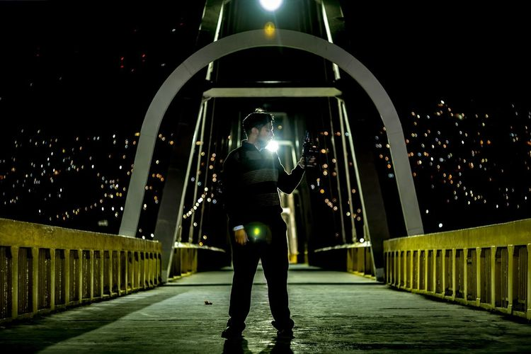 Man photographing while standing on bridge at night