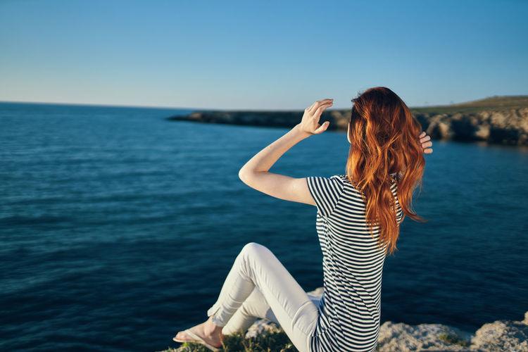 Woman sitting near sea against sky
