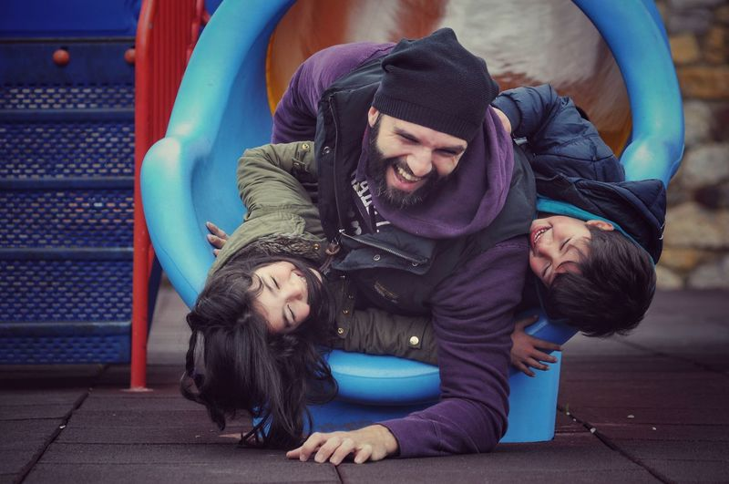 Happy Father With Children In Slide At Playground